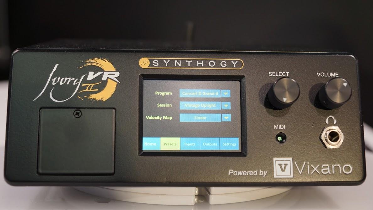 スタッフ OK | SynthogyからIvory II VR公開! 究極のピアノ音源をもっと軽快に、モバイルで  今年のSynthogyブースの白いピアノの上には何やら見慣れないボックスが。。。しかもパネルには液晶画面とIvory IIのロゴ?!